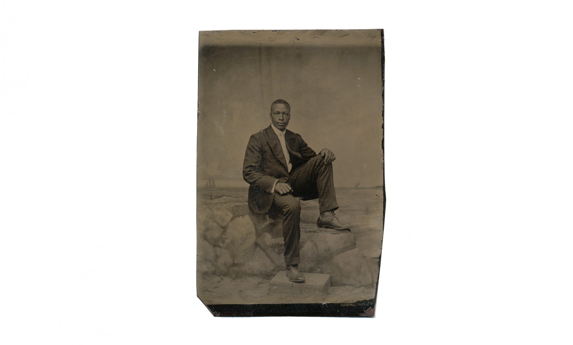 TINTYPE OF A YOUNG AFRICAN AMERICAN MAN SEATED ON A STONE WALL