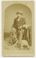 CDV OF A KANSAS HUNTER WITH HIS HUNTING DOG, SURROUNDED BY HIS HUNTING TROPHIES