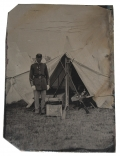 OUTDOOR 1880'S TINTYPE OF SOLDIER IN CAMP WITH STACKED MUSKETS
