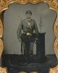 QUARTERPLATE TINTYPE OF ARMED UNION SOLDIER WITH US FLAG