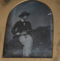 FULL PLATE DAGUERREOTYPE OF YOUNG BOY HOLDINIG A RIFLE